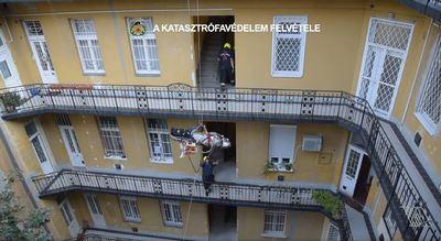 A negyedik emeletről, a gangon át eresztettek le egy sérültet a fővárosi tűzoltók - videó