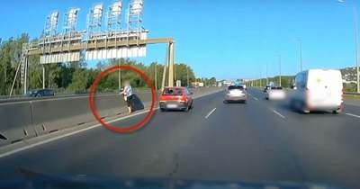 Megdöbbentő videó: átsétál, majd a beton elválasztón mászik át a nő a pályán